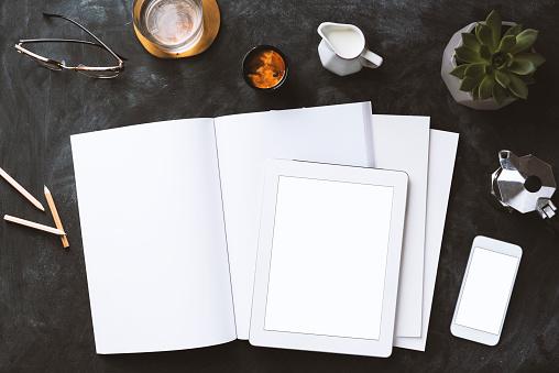 Flat lay blackboard desktop with magazine, blank screen smart devices