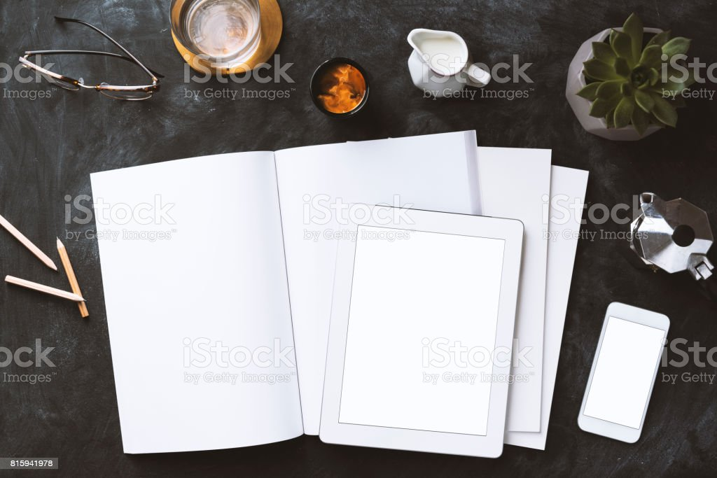 Flat lay blackboard desktop with magazine, blank screen smart devices stock photo