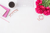 istock Flat lay blogger or freelancer workspace with a notebook, keyboard, red peonies on a white background 1161010971