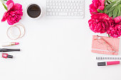 istock Flat lay blogger or freelancer workspace with a notebook, keyboard, red peonies on a white background 1163017950