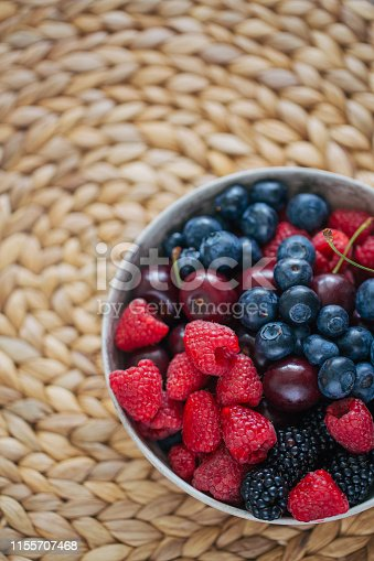 904734850istockphoto Flat lay bowl filled with summer berries on top of wicker mat. 1155707468