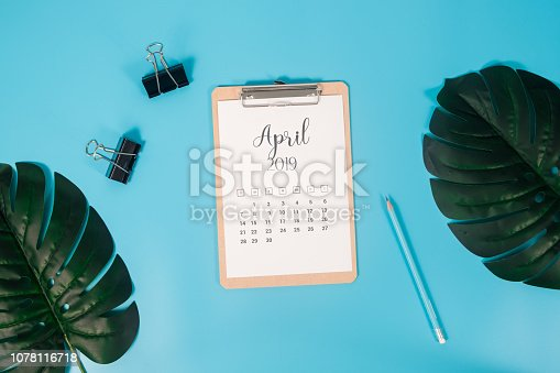 1124594277istockphoto Flat lay calendar with clipboard, palm leaves and pencil on blue background. April 2019. top view. 1078116718