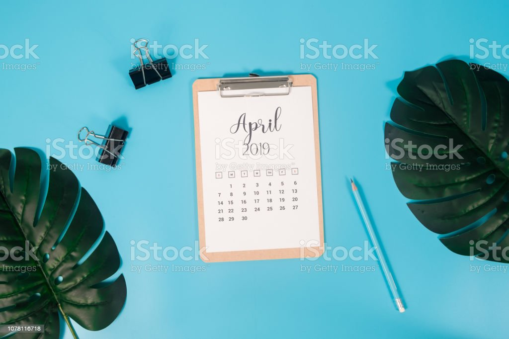 Flat lay calendar with clipboard, palm leaves and pencil on blue background. April 2019. top view. stock photo