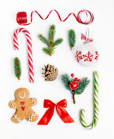 Flat lay Christmas composition with fir tree branches, gingerbread Christmas Cookie  and holiday ornament on white background. Top view.