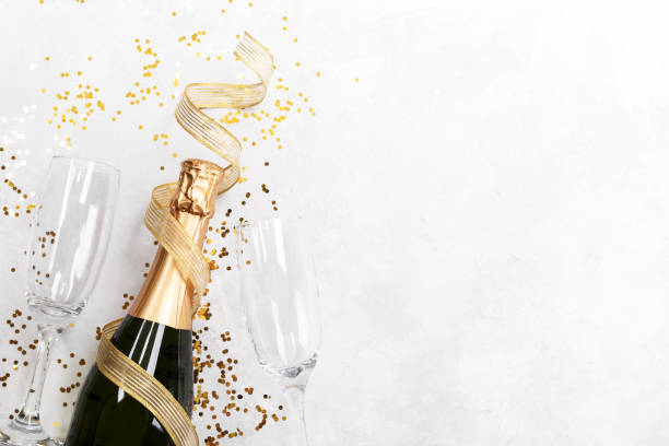 Flat lay composition of Champagne bottle and confetti Flat lay composition of Champagne bottle two glasses and confetti on grey stone background copy space champagne stock pictures, royalty-free photos & images