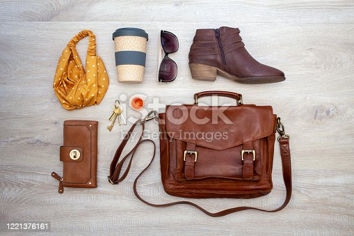 Knolling image of women's fashion and handbag essentials including leather bag and boots, purse, sunglasses, hair band, keys, lip balm, and a reusable coffee cup