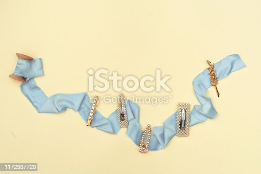 Flat lay composition with beauty trendy accessories hair pearl clip on yellow pastel background. Top view. Copy space fot text
