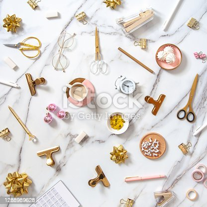 Flat lay composition with Christmas decoration objects, office stationery, alarm clock and coffee with marshmallows on white marble background. New Year 2021 and Christmas holidays preparation concept