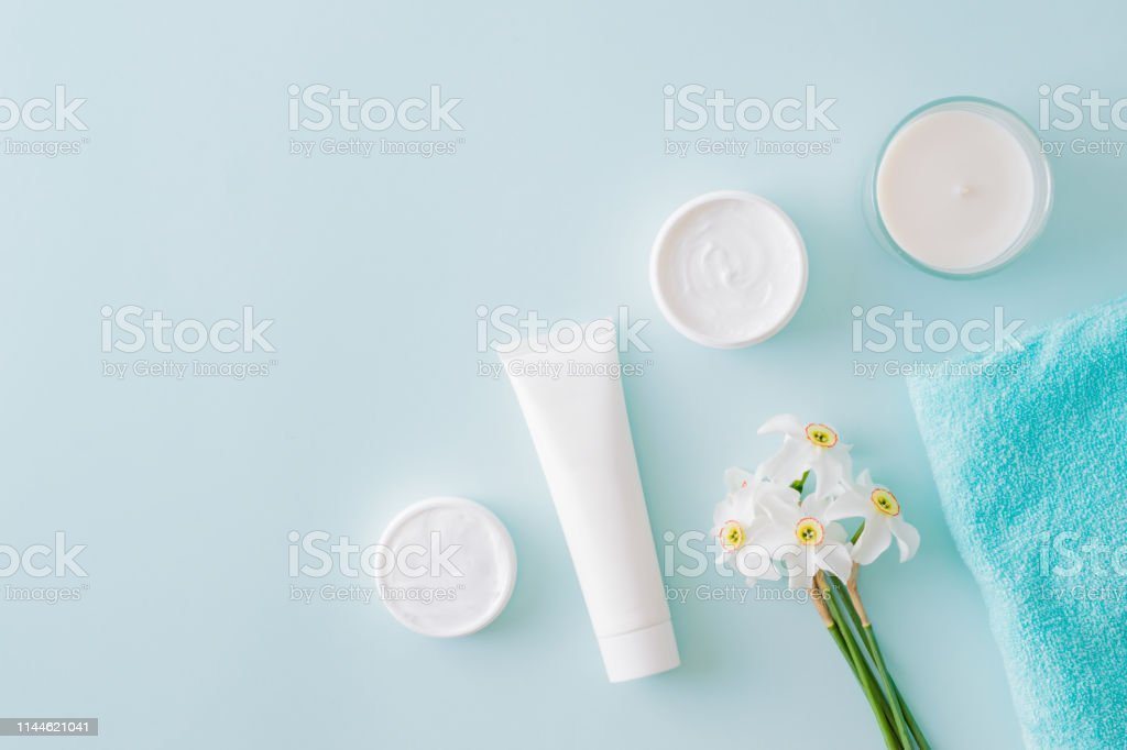 Flat lay composition with cosmetic products and white daffodils on a...