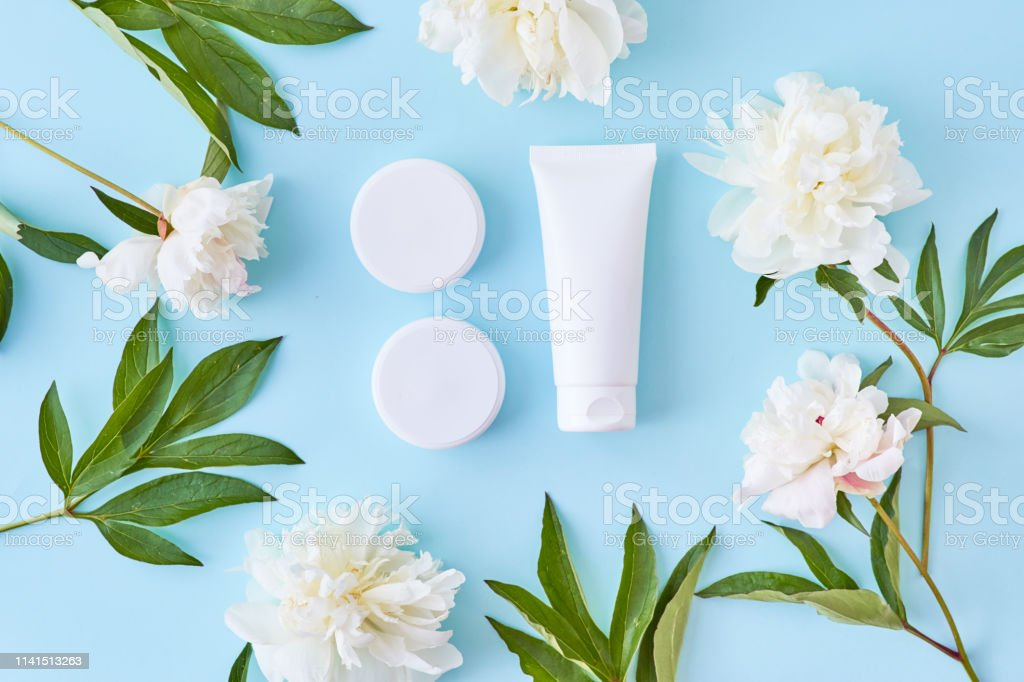 Flat lay composition with cosmetic products and white peonies on a...