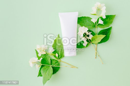 847096968 istock photo Flat lay composition with cosmetic products, mockup white tube and  jasmine flowers with green leaves on a green backgrounds 1157417601