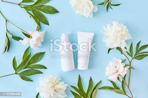 istock Flat lay composition with cosmetic products, mockup white tubes and white peonies on a blue background 1142264409