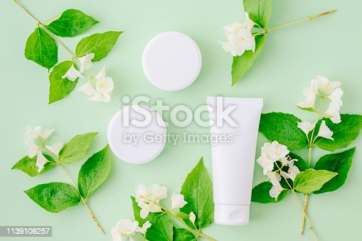 847096968 istock photo Flat lay composition with cosmetic products, mockup white tubes, jar of cream and  jasmine flowers with green leaves on a green backgrounds 1139106257
