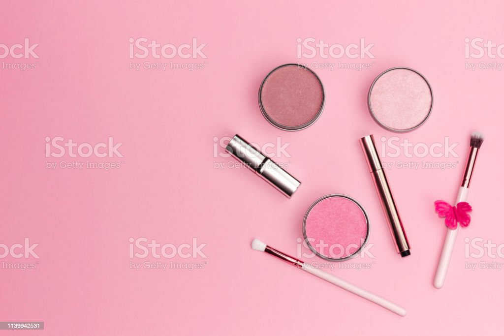 Flat lay composition with decorative makeup products on pastel pink...