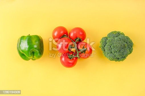 istock Flat lay composition with fresh fruits and vegetables on color background. Broccoli, tomato, pepper on yellow surface. Creative layout. 1280194309