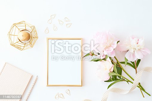 Flat lay composition with golden frame and light pink peonies on a white background
