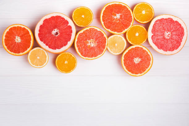 Flat lay composition with halves of different citrus fruits on white wooden background stock photo