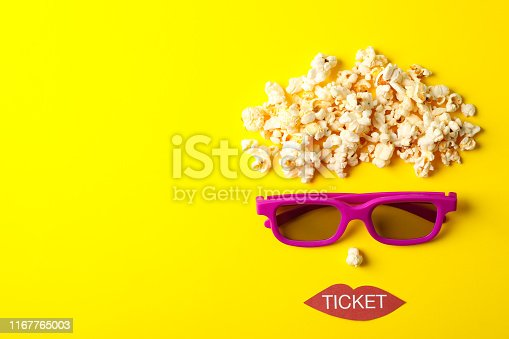 956942702 istock photo Flat lay composition with movie watching accessories on yellow background, top view 1167765003