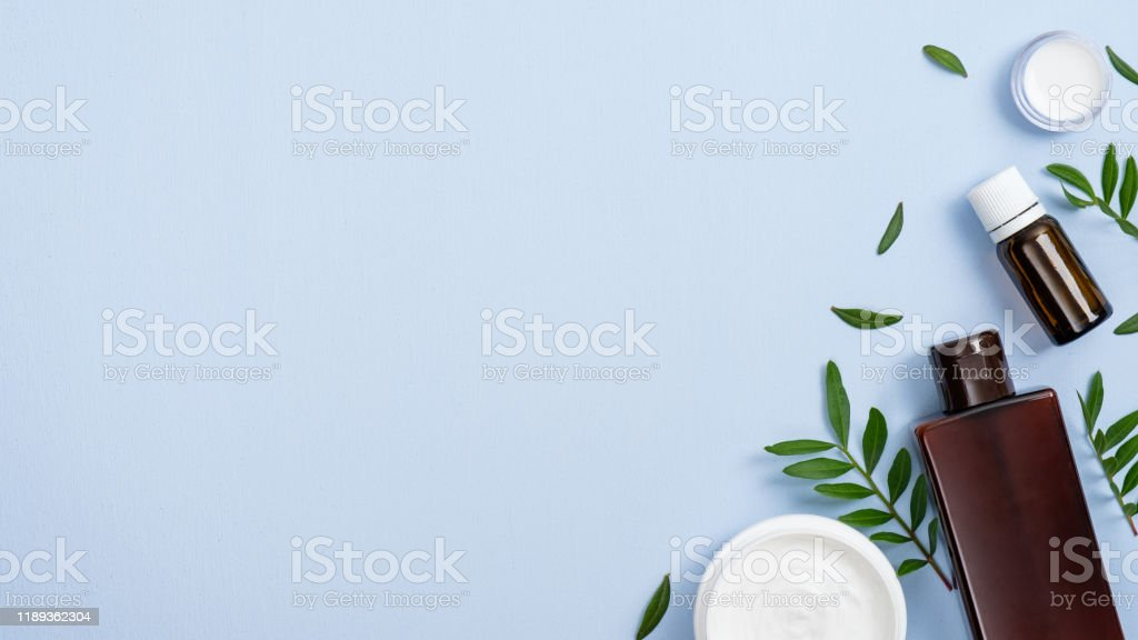 Flat lay composition with organic cosmetic products on blue...