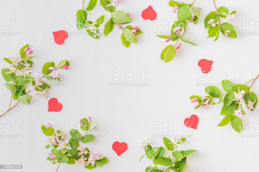 Flat lay composition with red hearts and blooming branches with green leaves on a white background stock photo