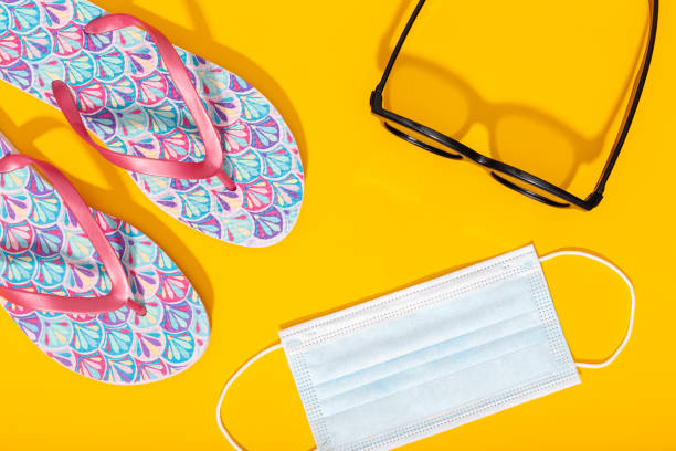 Flat lay composition with summer vacation accessories and face mask on yellow background stock photo
