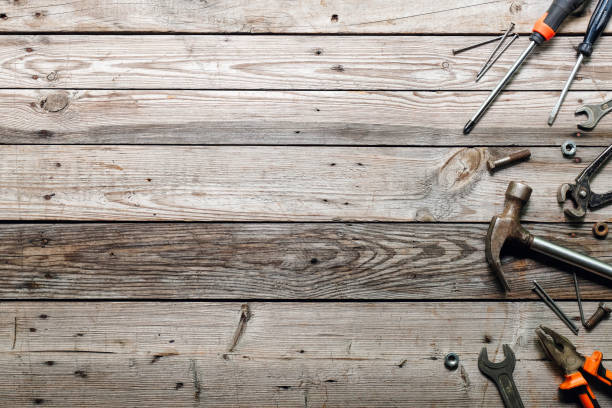 flat lay composition with vintage carpentry tools on rough wooden background. top view workbench with carpenter different tools. woodworking, craftsmanship and handwork concept. - fundo oficina imagens e fotografias de stock