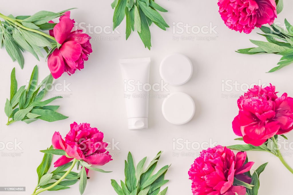 Flat lay composition with white cosmetic products and red peonies on...