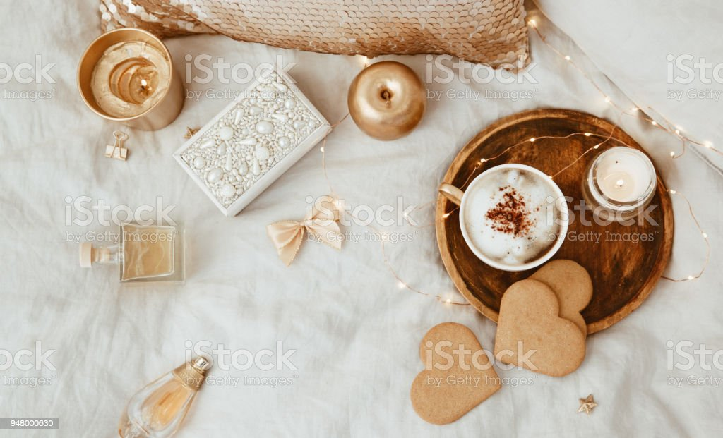Flat lay cozy lifestyle composition. Morning Coffee cup, cookies, gold decorations over linen bed