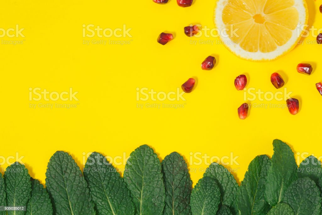 Flat lay creative summer background. Grass made of green mint leaves and sun with rays made of lemon and pomegranate on yellow background top view. Minimal summer concept stock photo