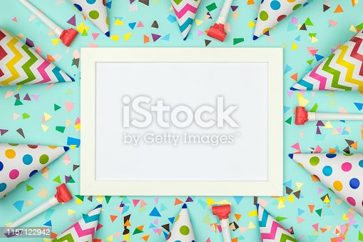 White frame on colorful table top view. Mockup for planning birthday or party. Copy space for text. Flat lay. Festive greeting background