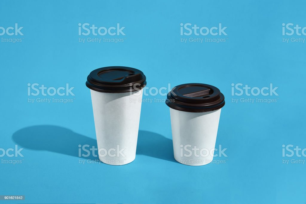 Flat lay design of 2 hot coffee cups on blue background with cop stock photo