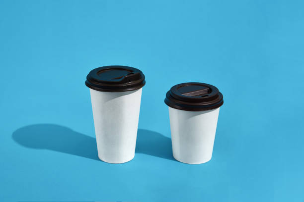 flat lay design of 2 hot coffee cups on blue background with cop - paper coffee cup stock photos and pictures
