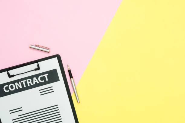flaches layout des büroarbeitsplatts arbeitsraum-top-ansicht eines vertragsdokuments und eines stifts auf rosa und gelbe pastellfarbe mit kopierraum. pastellfarbbildschirmarbeitel-arbeitsraum hintergrund. - rosa zitate stock-fotos und bilder