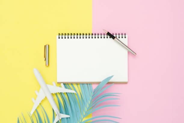 flache laien design der sommer reisekonzept - draufsicht mockup des leeren notizblock, stift, pastell kokos-blatt und flugzeug auf rosa pastell gelb bildschirm. reisen sie im sommer auf pastell farbigen hintergrund. - unterrichtsplanung vorlagen stock-fotos und bilder