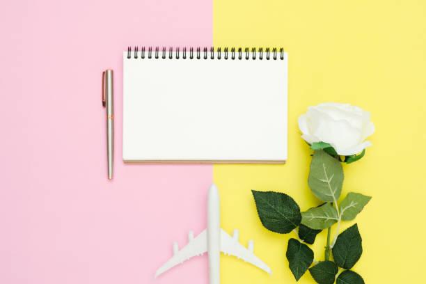 flaches laiendesign des reisesommer-konzepts-top-ansicht mockup von weißem papier-notebook, stationäre, flache und weiße rose auf rosa und gelbe pastell-farbbildschirm. reisen im sommer auf pastellfarbenem hintergrund - rosa zitate stock-fotos und bilder