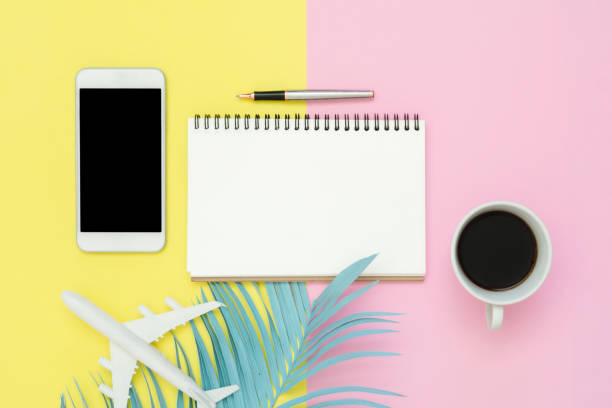 flach legen design der sommer reisekonzept - draufsicht des weißbuchs notebook, stift, mock-up smartphone, blaues blatt, kaffee und flugzeug auf rosa pastell gelb. reisen sie sommer auf pastell farbigen hintergrund. - pastellstifte stock-fotos und bilder