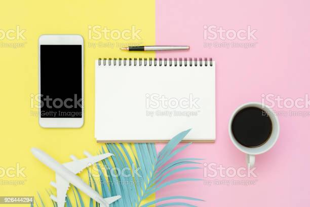 Photo of Flat lay design of travel summer concept - Top view of white paper notebook, pen, mock up smartphone, blue leaf, coffee and plane on pink yellow pastel color. Travel summer on pastel color background.