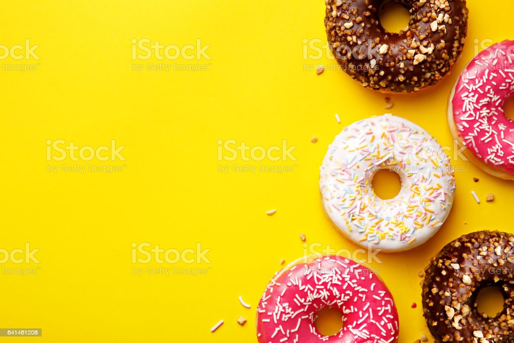 Flat lay donuts on a yellow background with copy space. Top view stock photo