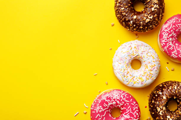flat lay donuts on a yellow background with copy space. top view - bombolone foto e immagini stock