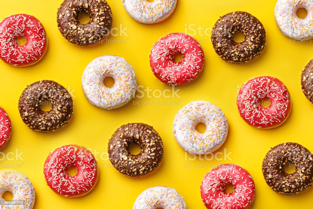 Flat lay donuts pattern on a yellow background. Top view stock photo