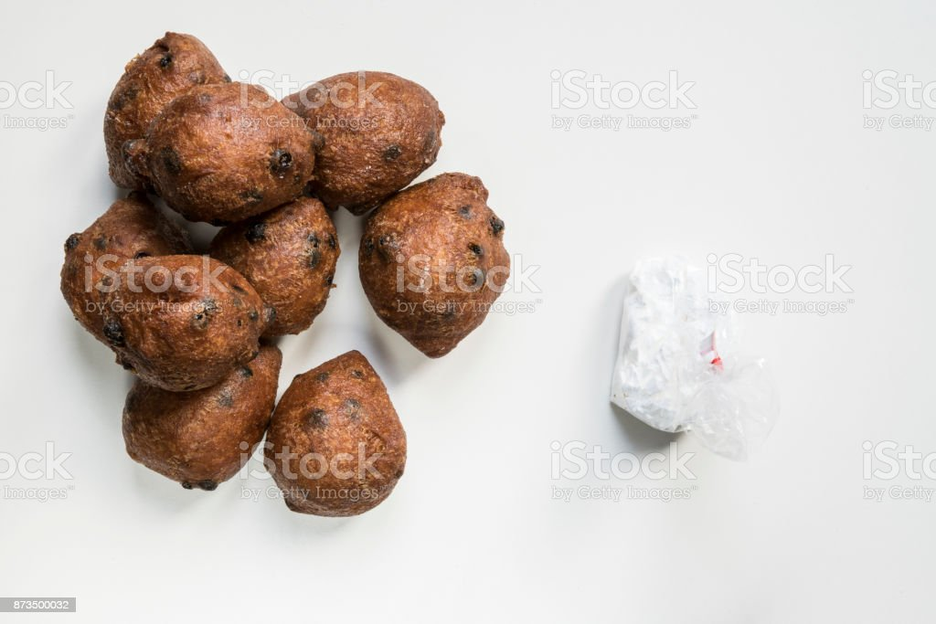 flat lay Dutch oliebollen, oil dumpling or fritter, for New Year's Eve, against white background stock photo