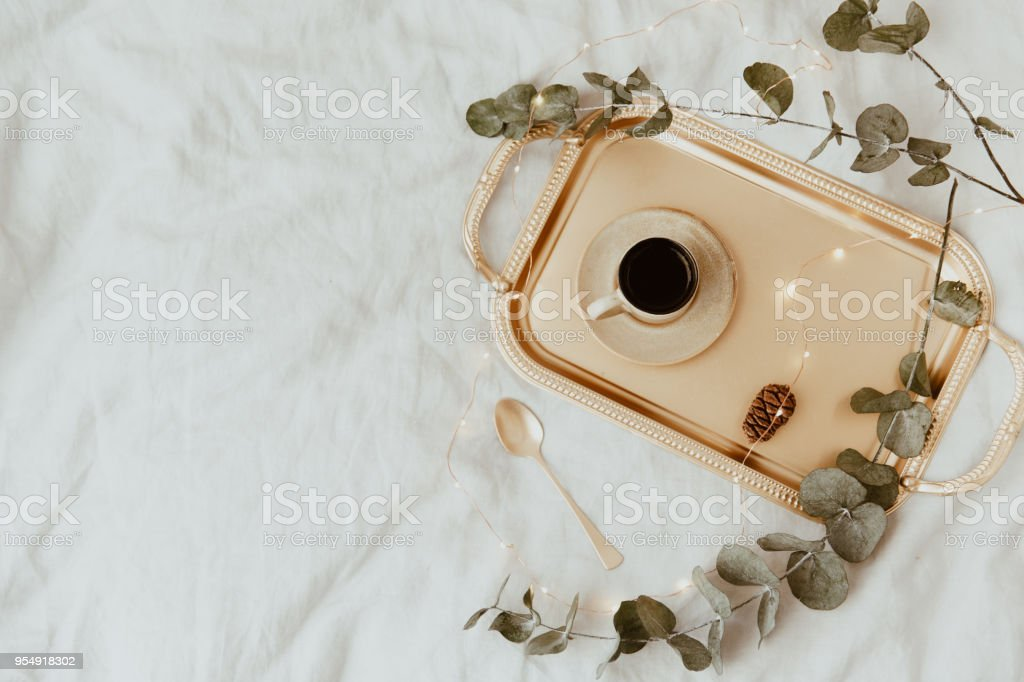 Flat lay elegant morning. Coffee cup on gold tray