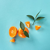 Top view of tropical exotic citrus fruits mandarine whole and slices with green leaves on a blue paper background