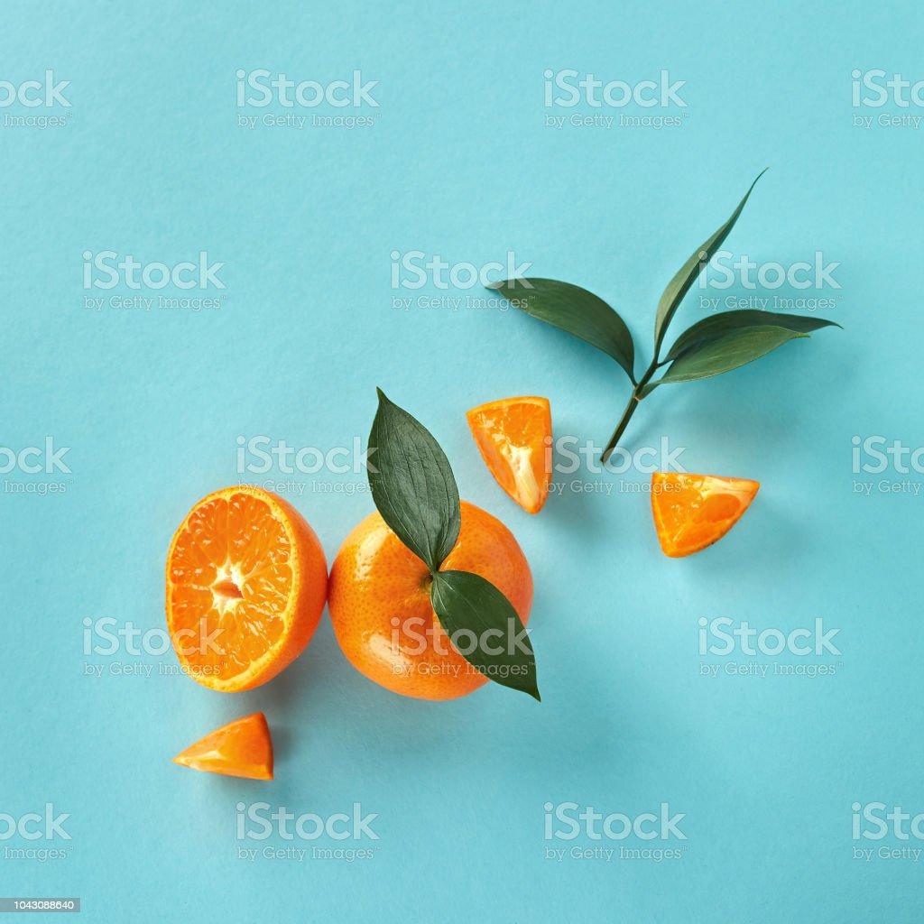 Flache Lay auf blauem Papierhintergrund exotische Zitrusfrüchte mit grünen Blättern. – Foto