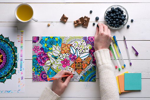 Flat lay, female coloring adult coloring books, stress relieving trend