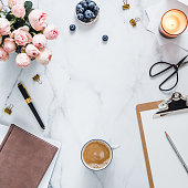 Top view of female home office with copy space in center. Clipboard, flowers, scented candle on white marble. Feminine home office mock up with copy space for text or design. Flat lay