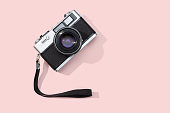 Flat lay film camera isolated on pink background. Copy space. Photography or photographer concept