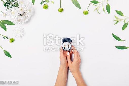 Flat lay floral arrangement female's hands holding small gift box with gold earrings among flowers and green leaves on white background, top view.