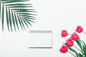 Flat lay floral arrangement of blank notebook