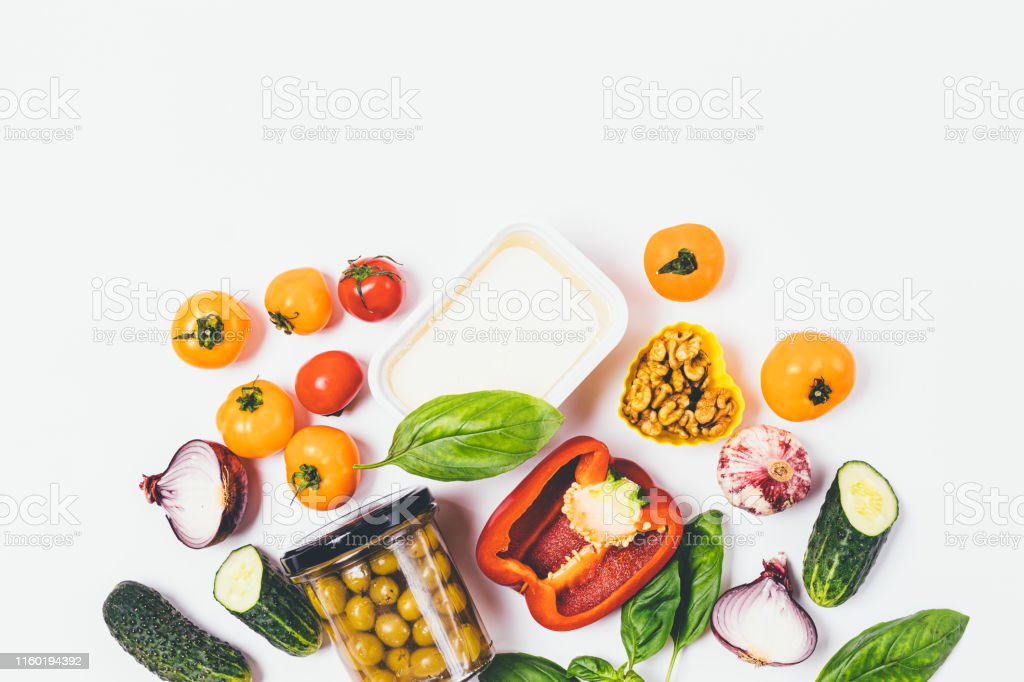 Flat lay food background of fresh vegetables, nuts and greens on...